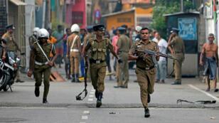 El 22 de abril de 2019, la policía de Sri Lanka despeja una zona en Colombo, mientras los oficiales del Equipo Especial de Bombas de la Fuerza de Tarea Especial inspeccionan el sitio donde una furgoneta estalló cerca de una iglesia que fue atacada el día anterior.