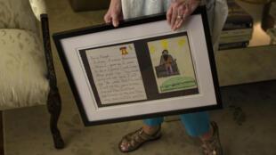 المعلمة السابقة لجورج فلويد تحمل صورة رسمها ونصا كتبه عندما كان في السابعة من العمر، في هيوستن بتكساس في 6 حزيران/يونيو 2020