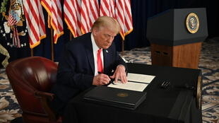 President Donald Trump signs executive orders extending coronavirus economic relief during a news conference at his golf club in  Bedminster, New Jersey, on August 8, 2020