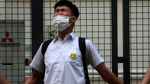 Un estudiante de secundaria hongkonés grita consignas en favor de los manifestantes y en contra del Gobierno mientras forma parte de una cadena humana.