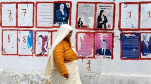 Una mujer pasa al lado de unos carteles electorales en Túnez, Túnez, el 9 de octubre de 2019.