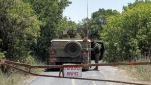 جندي إسرائيلي يقف أمام عربة عسكرية خلال دورية قرب الحدود مع سوريا في مرتفعات الجولان بتاريخ 1 تموز/يوليو 2018