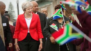La primera ministra del Reino Unido, Theresa May, es recibida por niños de la escuela que agitan banderas durante una visita a Ciudad del Cabo. 28/08/2018