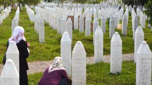 Des femmes cherchent des tombes de leurs proches dans le cimetière de Potocarion, près de Srebrenica en Bosnie, en juillet 2014.