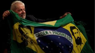 El expresidente de Brasil Luis Inácio Lula da Silva sostiene una bandera brasileña regalada por un partidario durante un evento en apoyo de su candidatura a la presidencia.