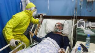 مسعف يعتني بمريض كوفيد -19 في مستشفى الشيخ راغب حرب الذي يحظى بدعم الهلال الأحمر الإيراني في مدينة النبطية بجنوب لبنان، 18 كانون الثاني/يناير 2021