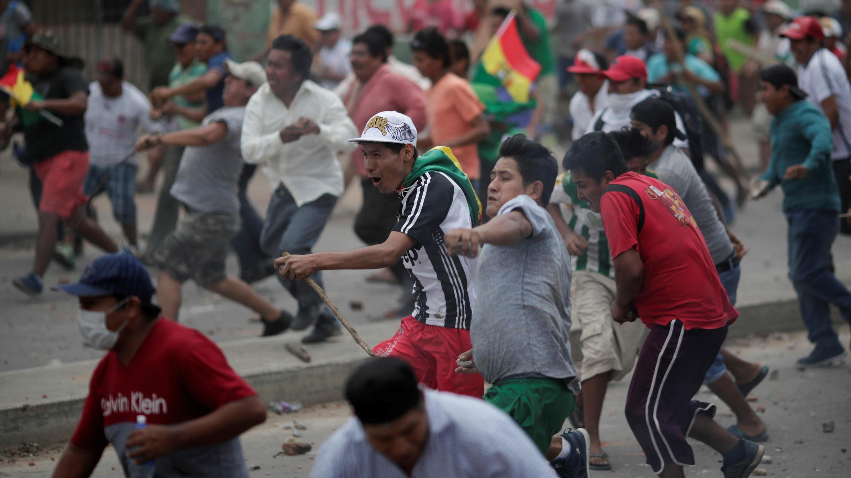 Grupos de manifestantes arrojan objetos durante los enfrentamientos entre simpatizantes y detractores del presidente Evo Morales en Santa Cruz de la Sierra, Bolivia, el 28 de octubre de 2019.