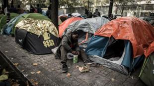 مهاجر يجلس بين الخيام في باريس في 26 تشرين الأول/أكتوبر 2016