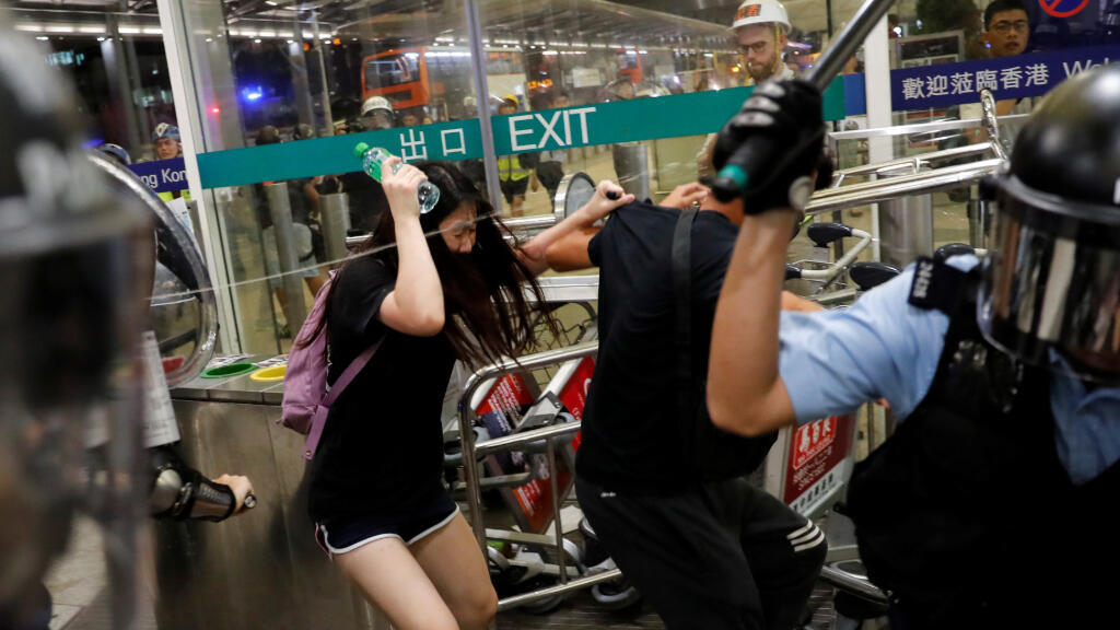 La policía antidisturbios utiliza gas pimienta durante una manifestación masiva después de que una mujer recibiera un disparo en el ojo, en el aeropuerto internacional de Hong Kong.