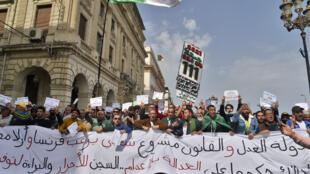 متظاهرون جزائريون يحملون لافتة كبيرة خلال تظاهرة للحراك الاحتجاجي في الجزائر العاصمة بتاريخ الثاني من نيسان/ابريل 2021