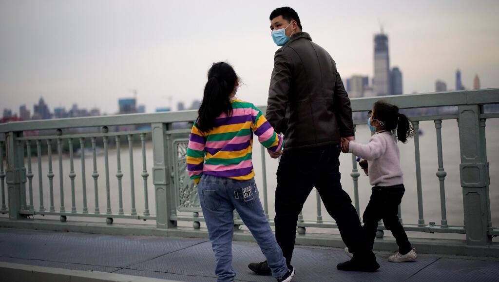 Estas personas caminan por la ciudad china de Wuhan el 28 de marzo de 2020. En los últimos dos días, China presentó más de 100 nuevos casos y todos provenían del exterior.
