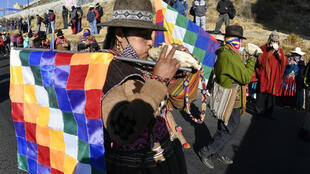 "Bolivian demonstrators blew large sea shell horns known as ""pututus"" during a march against the government of interim President Jeanine Anez"