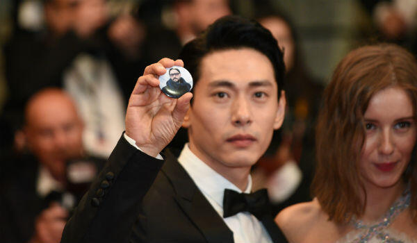 "South Korean actor Teo Yoo holds a picture of director Kirill Serebrennikov at the red carpet premiere of ""Leto""."