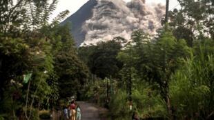 Habitantes observan como el monte Merapi, el volcán más activo de Indonesia, entra en erupción en Yogyakarta, el 27 de enero de 2021