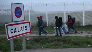"""Des migrants se dirigent vers le point de rassemblement pour quitter la """"jungle"""" de Calais le 24 octobre 2016."""