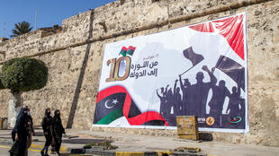 """Une banderole dans le centre de la capitale libyenne Tripoli, le 16 février 2021, sur laquelle on peut lire en en arabe """"17 février - de la révolution à l'état"""", un jour avant les commémorations du 10e anniversaire du soulèvement contre Mouammar Kadhafi."""