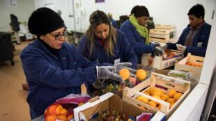 Des bénévoles d'une association Andes recueillent des fruits invendus à Rungis, le 21 novembre 2017, afin de les distribuer à des personnes dans le besoin.