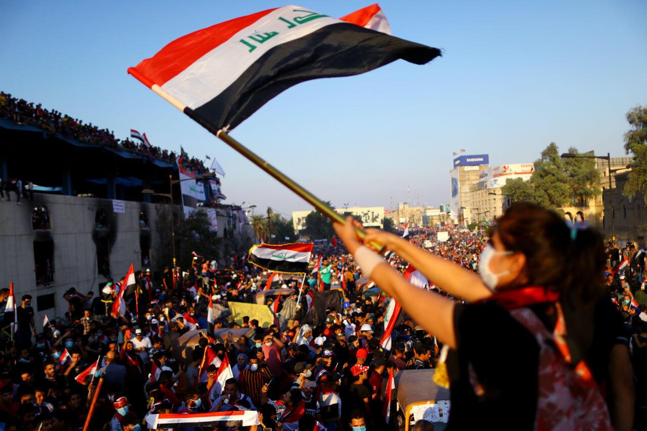 سيدة تلوح بالعلم العراقي وسط مظاهرة في ساحة التحرير بالعاصمة بغداد.