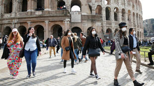 People wearing protective masks walk past the Colosseum in Rome on February 25, 2020.