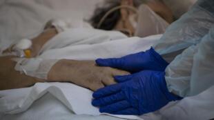 La Dr Moyra Lopez tient la main d'un patient, atteint du coronavirus, quelques instants avant son décès, le 22 juillet 2020 à l'hôpital Barros Luco de Santiago du Chili
