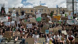 Jóvenes manifestantes sostienen pancartas contra el cambio climático durante una protesta de 'viernes por el clima' frente al Parlamento griego en Atenas, el 24 de mayo de 2019.