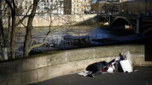 Un sans-abri dormant près de la Seine, en face de l'île Saint-Louis, le 28 décembre 2017, à Paris.