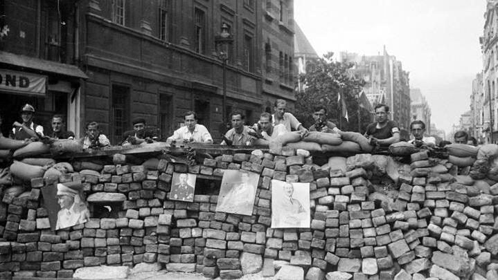 Des FFI prennent position derrière une barricade dans une rue de Paris, en août 1944.