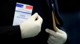 Un électeur porte des gants en latex pour aller voter aux élections municipales à Paris, le 15 mars 2020.