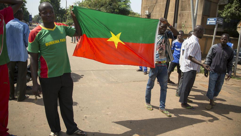 Des Burkinabè brandissent le drapeau du Burkina Faso dans les rues de Ougadougou, le 22 septembre 2015.