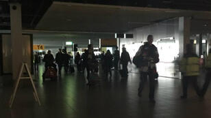 Passengers walk through a darkened Schiphol airport in Amsterdam during the power cut