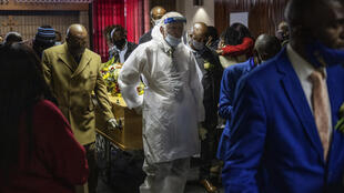 An undertaker wears a protective suit for a funeral in Johannesburg. South Africa has the highest numbers of diagnosed infections in Africa