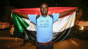 """Un manifestant soudanais porte un T-shirt sur lequel est écrit """"Révolutionnaires... libres"""" et """"déchu"""", avec la date du jour, en référence à la destitution d'Omar el-Béchir par l'armée."""