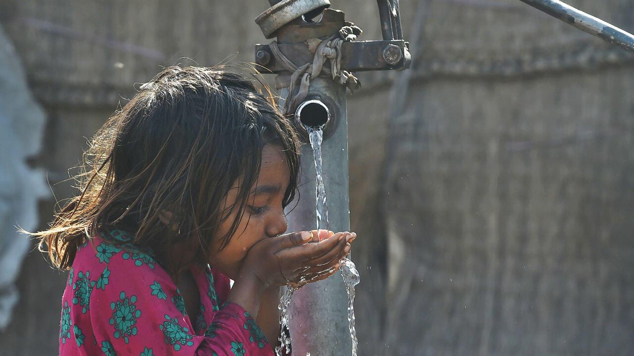 Una niña pakistaní bebe agua de una bomba manual de agua en Lahore el 22 de marzo de 2019, en el Día Mundial del Agua.