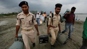Personal de seguridad y oficiales electorales transportan el material para las elecciones luego de llegar en ferry a Nimatighat, distrito Jorhat, en el estado nororiental de Assam, India, el 9 de abril de 2019.