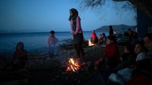 Migrantes de Afganistán que llegaron en un bote en una playa en los últimos dos días después de cruzar parte del Mar Egeo desde Turquía hasta la isla de Lesbos, se calientan junto a una hoguera cerca del pueblo de Skala Sikamias, Grecia, el 2 de marzo de 2020.