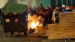 Los manifestantes se esconden detrás de barricadas improvisadas mientras otros corren durante una protesta en La Paz, Bolivia, el 31 de octubre de 2019.