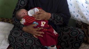 امرأة أفغانية ترضع قريبها الطفل محمد علي الذي فقد أمه في هجوم على مستشفى الولادة الذي تديره منظمة أطباء بلا حدود في كابول، في ضواحي العاصمة في 22 أيار/مايو 2020.