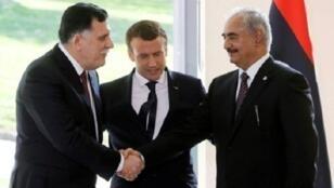 الرئيس الفرنسي إيمانويل ماكرون يتابع مصافحة بين رئيس حكومة الوفاق الوطني الليبية فائز السراج وقائد قوات شرق ليبيا المشير خليفة حفتر اثر اجتماعهما قرب باريس في 25 تموز/يوليو 2017.