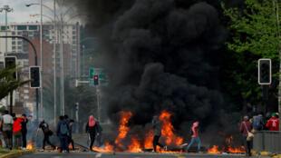 Des manifestants près d'une barricade en feu à Concepcion, au Chili, le 20 octobre 2019.