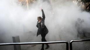 إيرانية تحاول الاحتماء من الغاز المسيل للدموع خلال تظاهرة في طهران في 30 كانون الأول/ديسمبر 2017