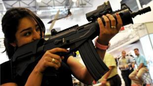 Una mujer sostiene un rifle de batalla durante la feria Expodefensa en Cali, Colombia, el 16 de abril de 2010.