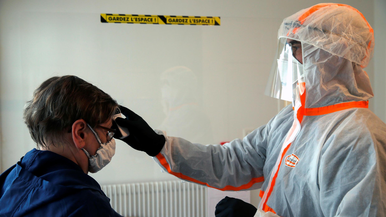 Un médico francés que usa un traje de protección verifica la temperatura de una mujer en un sitio de prueba para detectar la enfermedad del nuevo coronavirus, en Gouzeaucourt, Francia, el 28 de abril de 2020.