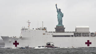 The hospital ship USNS Comfort passes the Statue of Liberty as its departs New York City