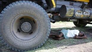 Un homme se repose à l'ombre sous un camion en banlieue d'Hyderabad le 25 mai.