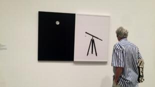 """Un homme regarde l'""""Atlas Photographique de la lune"""" de Maurice Loewy et Pierre Henri Puiseux, le 1er juillet 2019"""