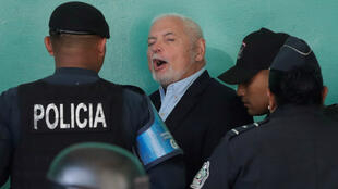 Oficiales de policía custodian al expresidente panameño, Ricardo Martinelli, en su llegada al juzgado para la reanudación del proceso en su contra en Ciudad de Panamá, el 22 de marzo de 2019.