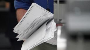 Un employé portant des bulletins de vote avant un nouveau dépouillement, le 12 novembre 2018, à Lauderhill en Floride.
