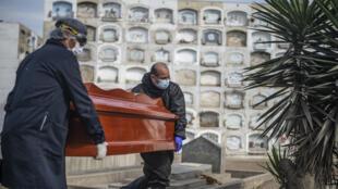 Empleados sacan un ataúd con el cuerpo de una víctima de COVID-19 de un contenedor refrigerado antes de su cremación en el cementerio El Ángel, en Lima, el 6 de mayo de 2020