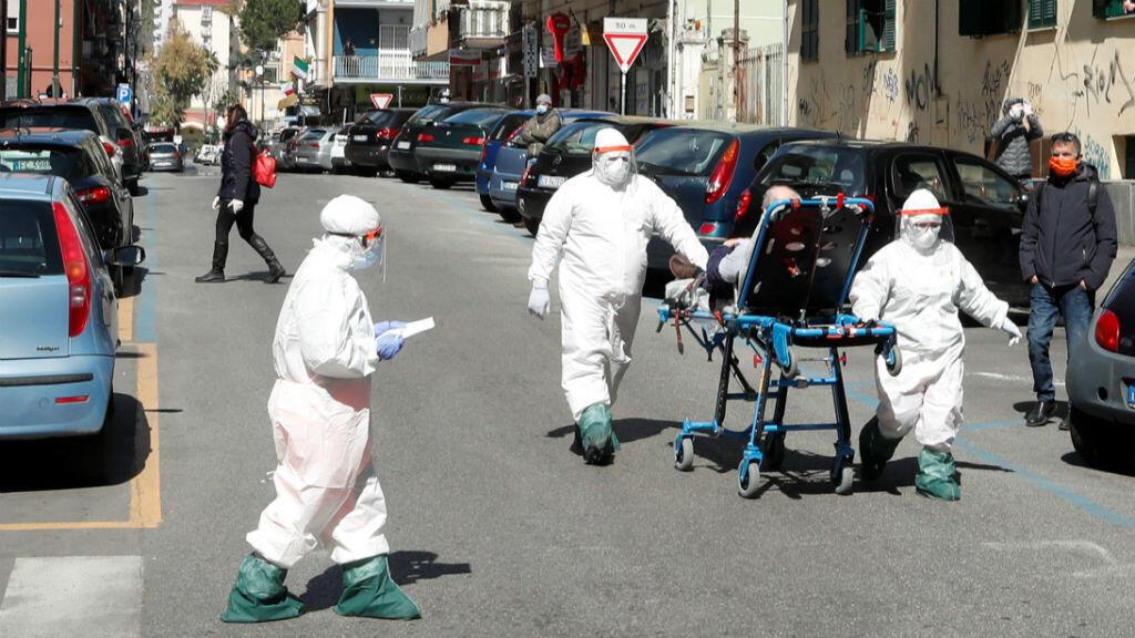 El personal médico con equipo de protección completo lleva a un paciente en una camilla por una calle en Nápoles, Italia, mientras continúa la propagación de la enfermedad por coronavirus Covid-19, el 2 de abril de 2020.