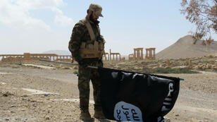 Un soldat syrien tient dans sa main un des drapeaux de l'organisation État islamique, le 27 mars 2016.